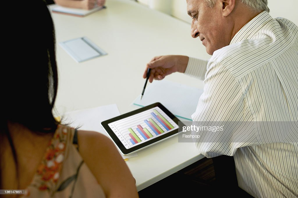Two business people using digital tablet : Stock Photo