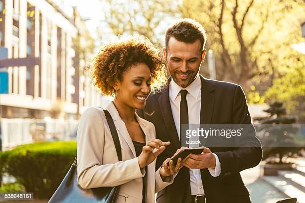 Deux hommes d'affaires à l'aide de téléphone intelligent en plein air