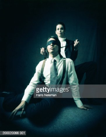Two Business people woman behind man with blindfold