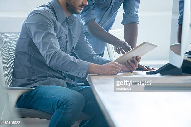 Dos hombres de negocios trabajando con una tableta digital.