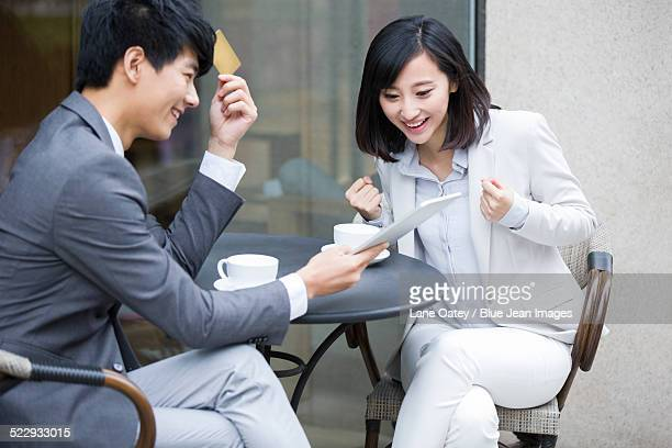 Two business person sitting at outdoor sidewalk caf¨¦