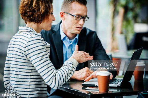 Two business travellers having a meeting at an airport cafe