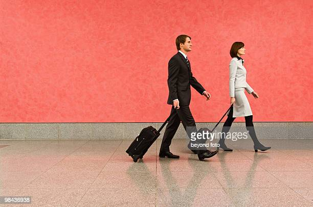 two business travellers in corridor pulling carry-on suitcases