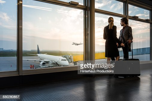 Two Business Travellers Staning At Airport Window