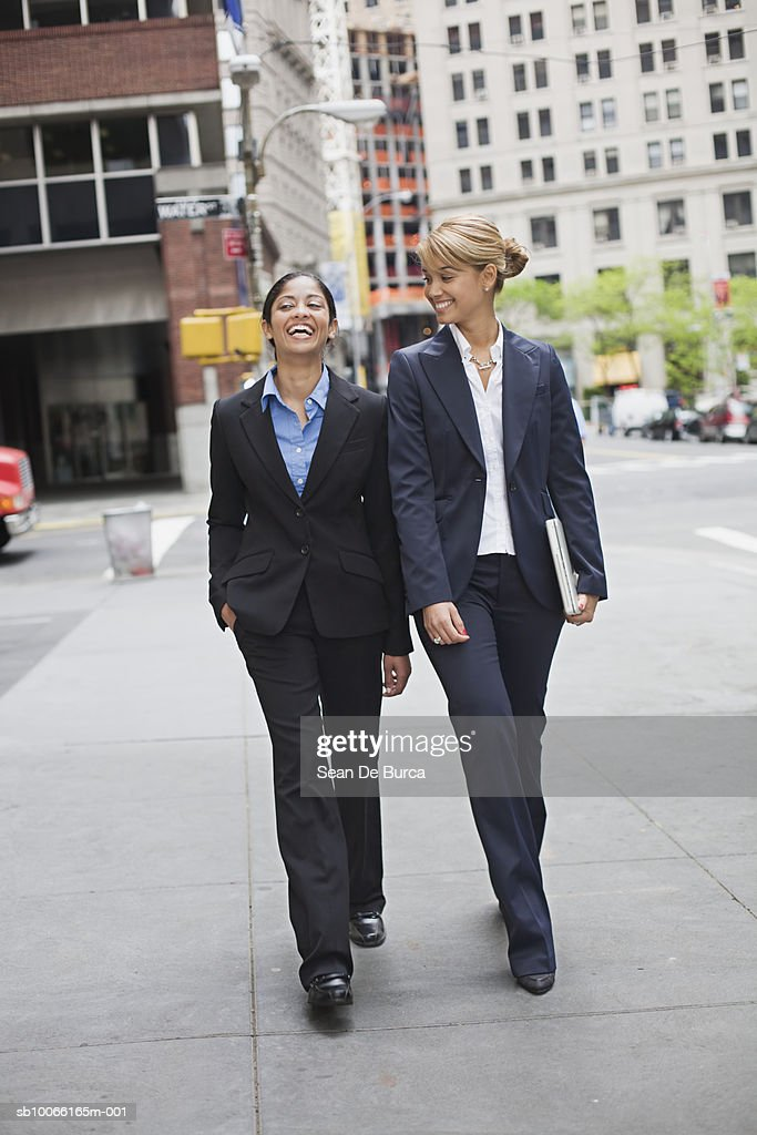Two business woman waling street, laughing : Stock Photo