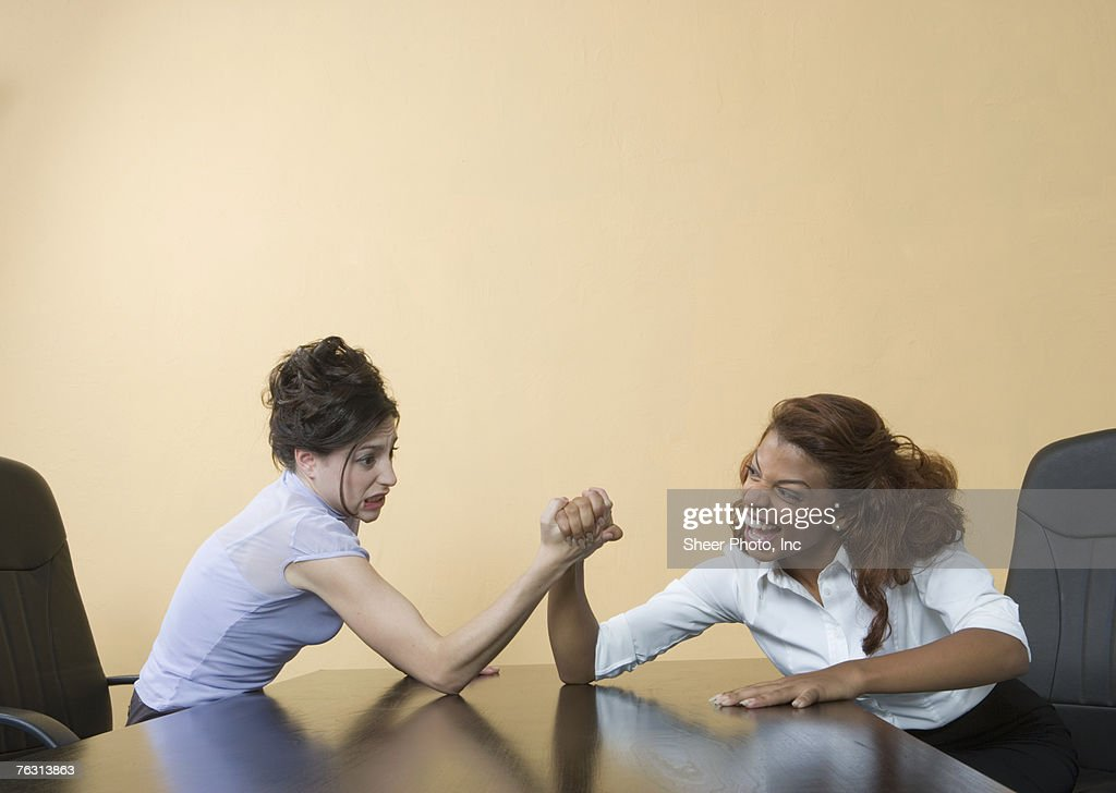 Two business women arm wrestling, indoors : Stock Photo