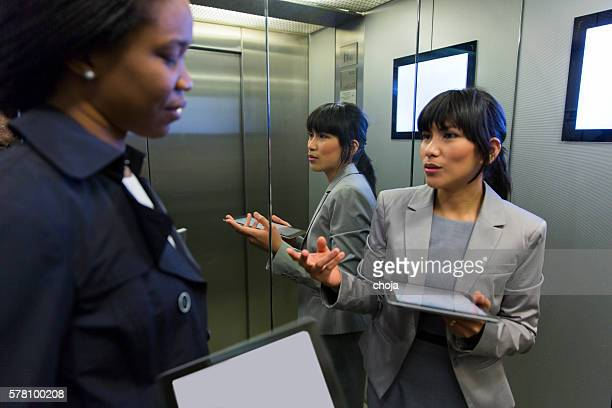 Two business women in elevator discussing,using digital tablets
