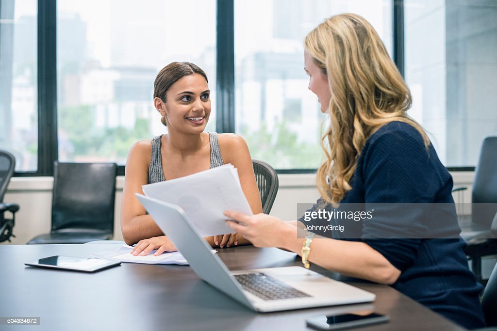 Two business women in modern office discussing with laptop : Stock Photo