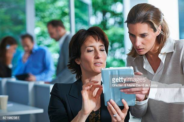 Two business women looking at digital tablet in office