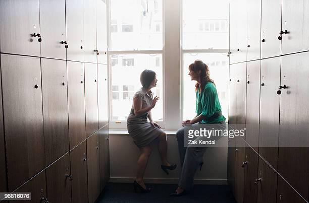 Two business women talking in a locker