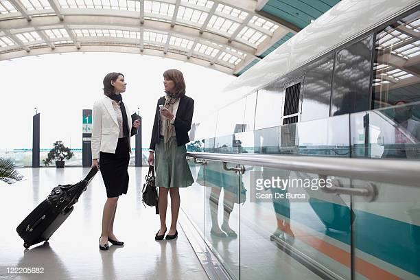 Two business women talking on a train platform.