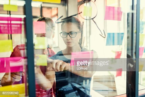 Two business women working together on wall glass : Stock Photo