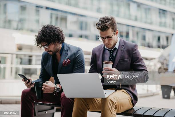 Two businessman are using their devices to surf the net on the coffee break