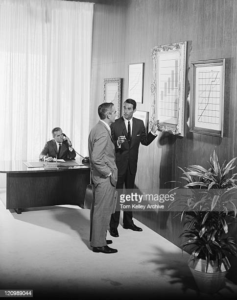 Two businessman discussing at bar chart while another man using telephone in background