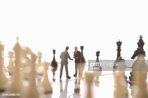 Two businessman figurines atop chess board (focus on figurines)