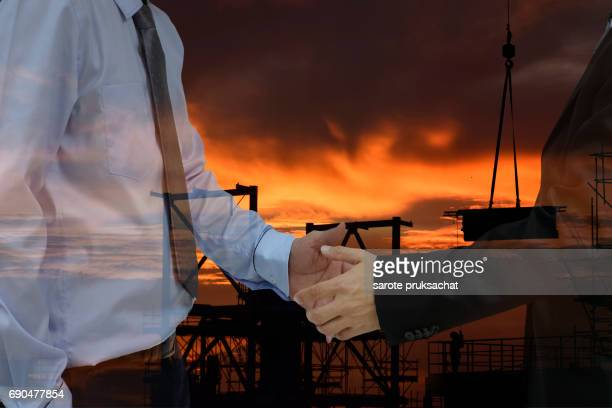 Two businessman  hand shake for business  success concept and construction background .