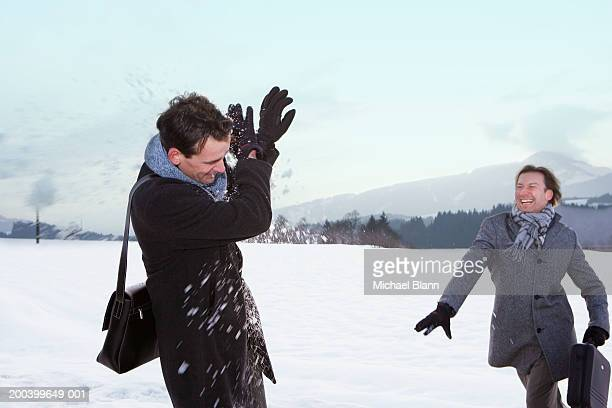 Two businessman having snowball fight in winter landscape, smiling