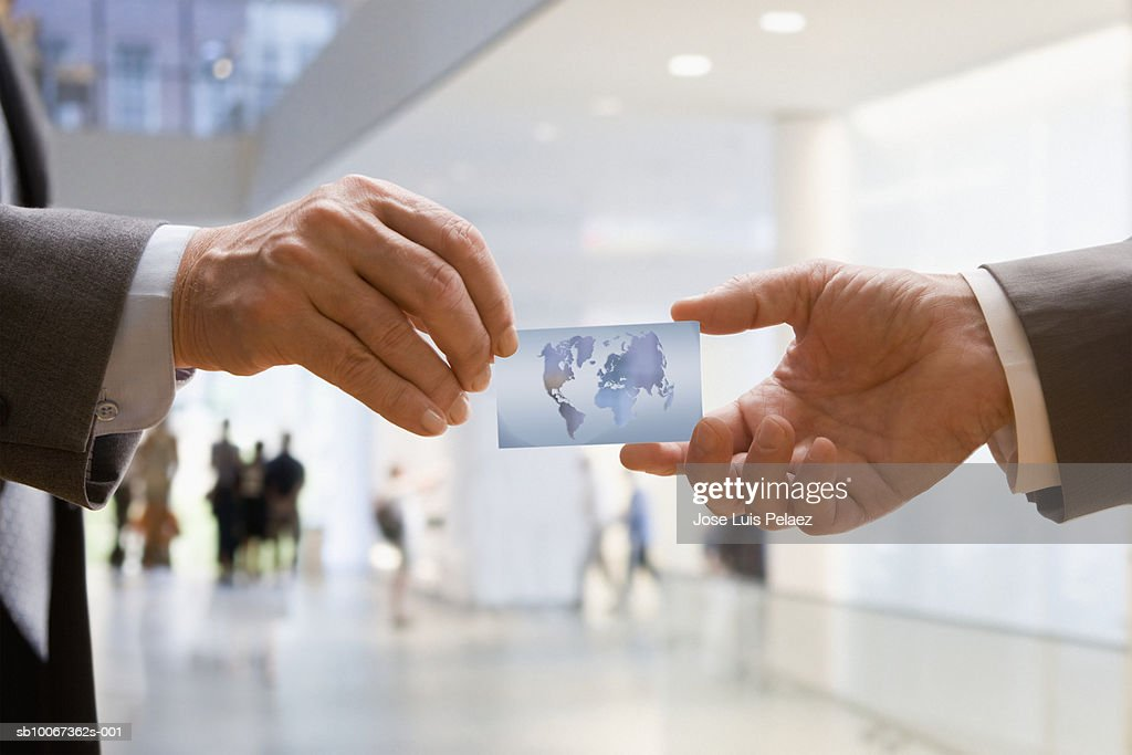 Two businessman passing business card, close-up : Stock Photo