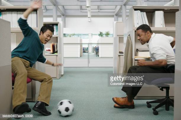 Two businessman playing football in an office
