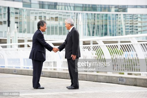 Two businessman shaking hands on a bridge