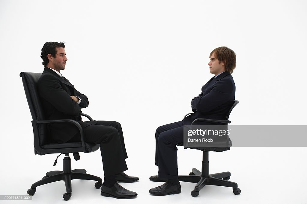 Businessman sitting on office chairs staring at each other side view