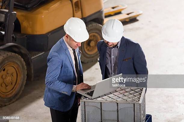 Two Businessman Working in Factory