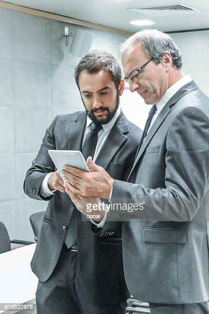 Two businessman working on mobile device