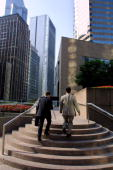 Two businessmen almost dwafted by surrounding highrise buildings make a flight of steps near Exchange Square in Central Hong Kong 06 February 2001...