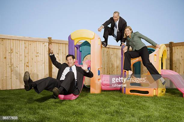 Two businessmen and a businesswoman playing with jungle gym