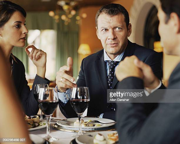 Two businessmen and businesswoman at restaurant table, close-up