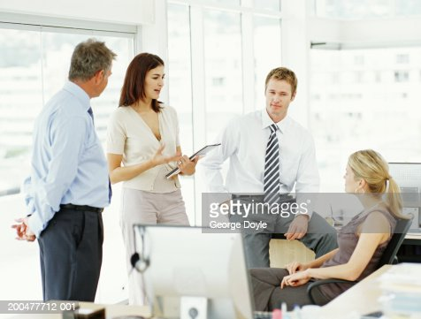 Two businessmen and two businesswomen having discussion in office : Stock Photo