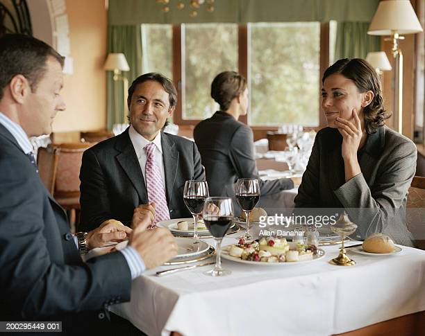 Two businessmen and woman at restaurant table, smiling