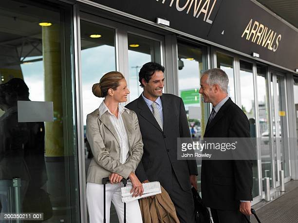 Two businessmen and woman meeting at airport