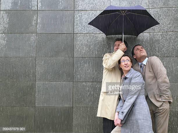 Dos empresarios y mujer compartir paraguas de lluvia