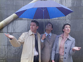 Two businessmen and woman sheltering under umbrella in rain