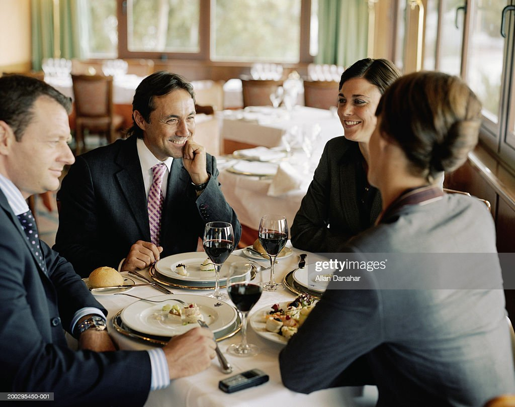 Two businessmen and women at restaurant table, laughing : Stock Photo
