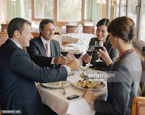Two businessmen and women at restaurant table, raising glasses