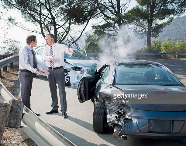 Two businessmen arguing about damaged cars