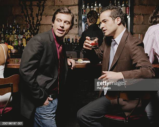 Two businessmen at bar, looking away