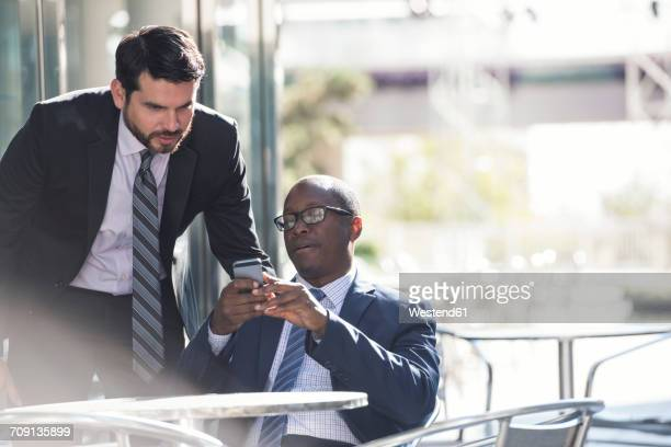 Two businessmen at outdoor cafe looking at cell phone