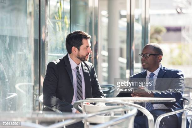 Two businessmen at outdoor cafe with tablet
