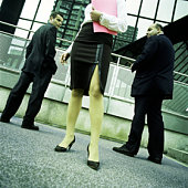 Two businessmen, backs turned, heads turning to look at woman.