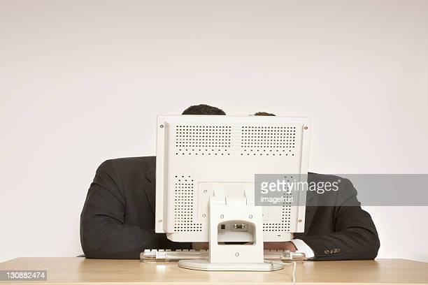 Two businessmen behind a computer monitor, absorbed