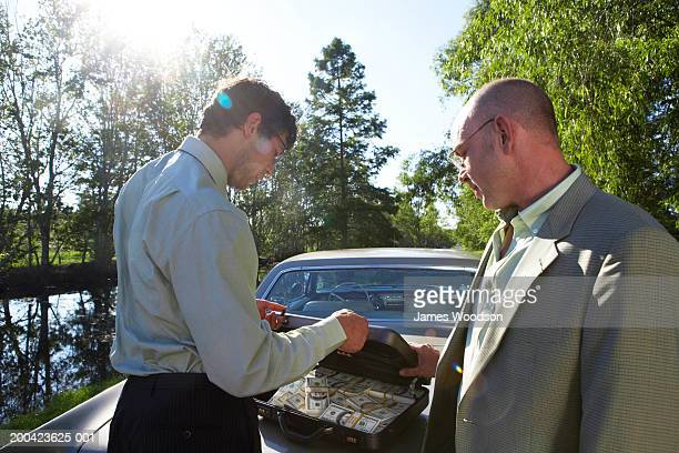 Two businessmen behind car with money in briefcase, close-up