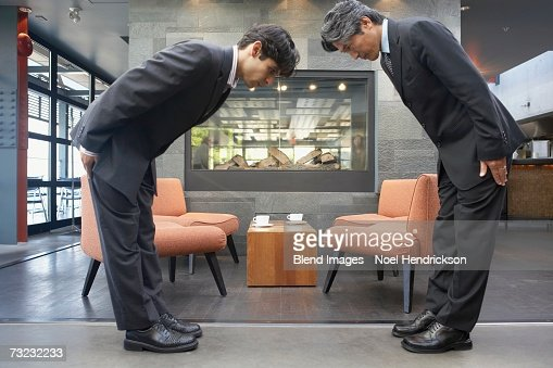 Two businessmen bowing to each other in cafe : Stock Photo