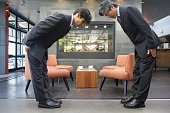 Two businessmen bowing to each other in cafe