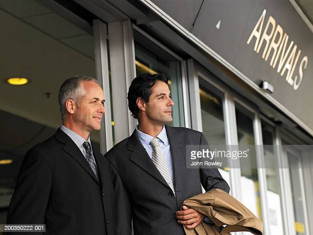 Two businessmen by arrivals sign in airport