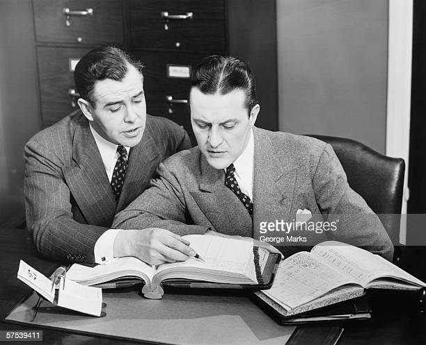 Two businessmen checking trading books, (B&W)