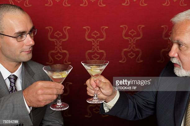 Two businessmen clinking glasses with martini