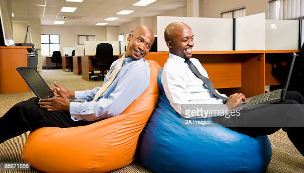 Two businessmen compare work on laptops while sitting on beanbags. Pretoria, South Africa